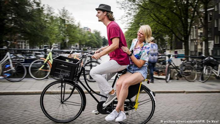Niederlande Amsterdam 2 Menschen auf Fahrrad (picture-alliance/dpa/ANP/R. De Waal)