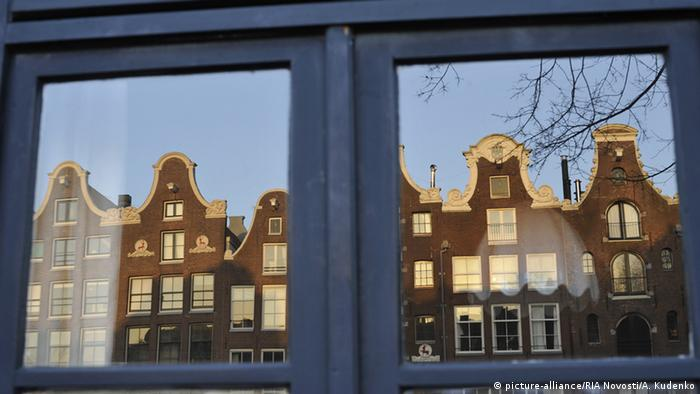 Traditional Amsterdam houses with gables reflected in a window.