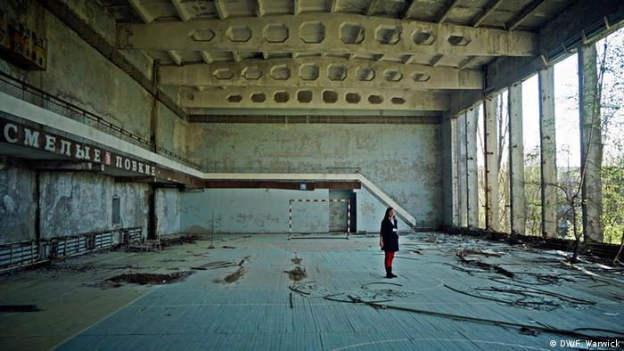 Tour guide Vita Polyakova stands in a derelict sports hall in Pripyat