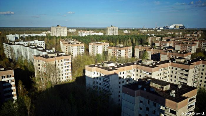 An aerial shot of the abandoned Ukrainian city of Pripyat, with the Chernobyl nuclear power plant visible in the background (DW/F. Warwick)