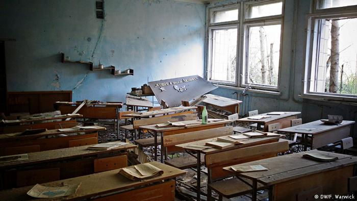An abandoned and dusty school room with overturned desks