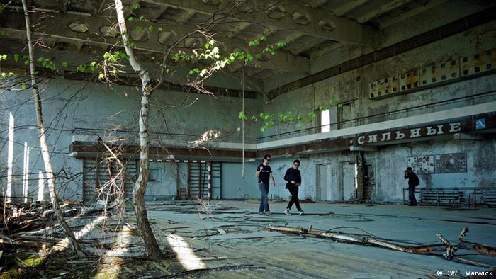 A tree grows out of the floor of a derelict sports hall through which several tourists walk