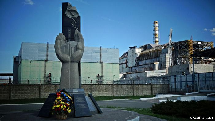 A memorial to the lost workers is blanked by Chernobyl reactor number four enclosed in a rusty sarcophogus
