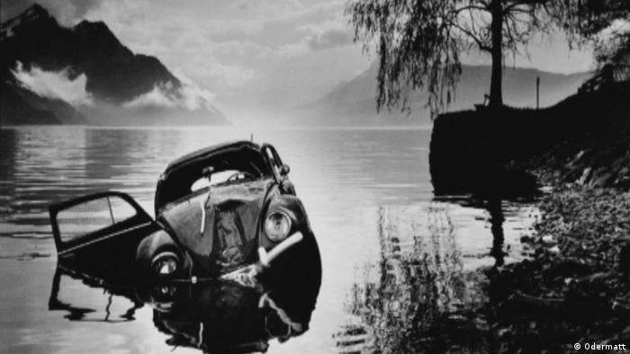 Ein schwarzweißes Unfallfoto des Schweizer Fotografen Arnold Odermatt zeigt einen verbeulten VW-Käfer in einem See. (Foto: Odermatt)