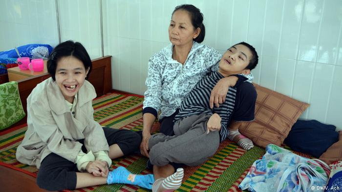 Eine Mutter mit zwei Kindern, die Missbildungen durch Agent Orange erlitten haben.