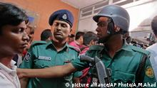 Bangladeshi policemen try to control the crowd of onlookers at a building where two people were found stabbed to death in Dhaka, Bangladesh, Monday, April 25, 2016 (AP Photo/A.M.Ahad)