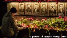 Ukraine Kiew Mann und Blumen bei Gedenken an Tschernobyl