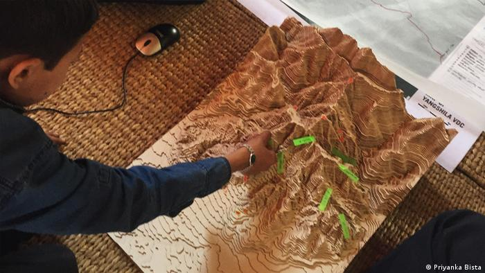 Photo: A laser cut model of Yangshila used to point out the Learning Grounds plots