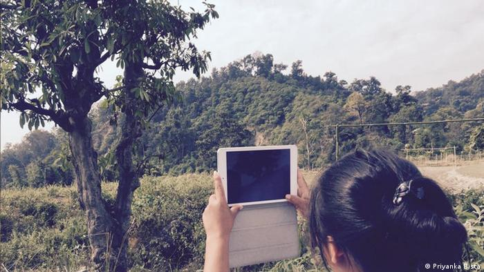 Photo: A young woman is holding up an iPad in a mountainous, wooded area.
