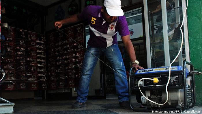 A man manipulates a power generator during a power cut at a store in the border state of San Cristobal, Venezuela