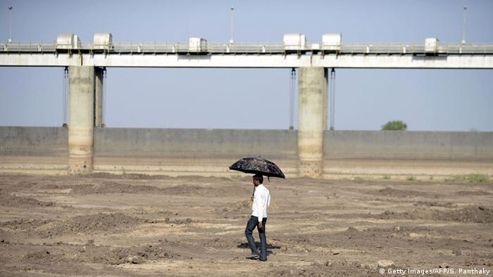 An Indian man holds an umbrella as he walks on the dry reservoir bed next to Gunda Dam