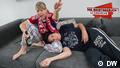 Frau und Mann auf Mann auf dem Sofa. Sie hält eine Flasche Bier in der Hand und trägt einen Fußball-Schal, er kuschelt sich an sie.