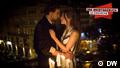 Sich umarmendes Paar mit Kerzen im Vordergrund