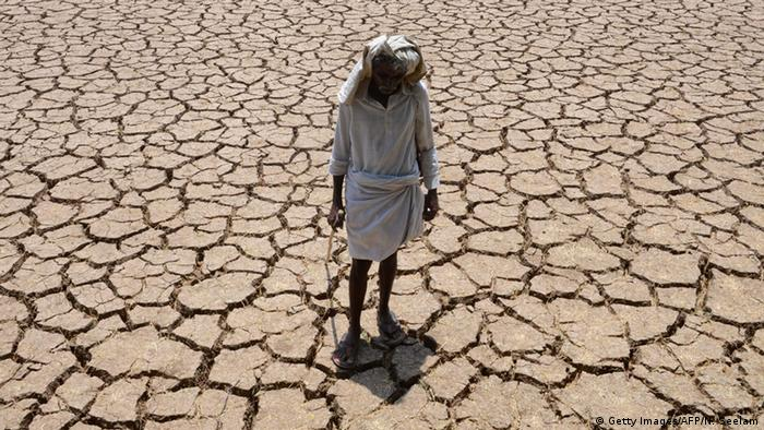 An Indian farmer poses in his dried up cotton field