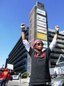 A person lifts their arms in protest in front of a building