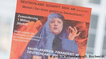 An AfD sign depicts Merkel wearing a head scarf