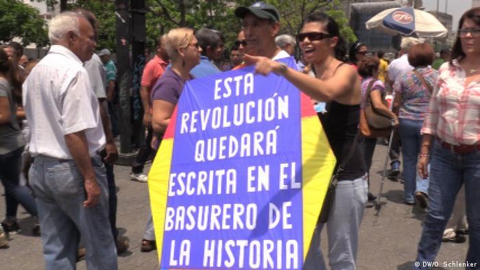 Esta revolução ficará escrita na lixeira da história, diz cartaz de manifestante anti-Maduro