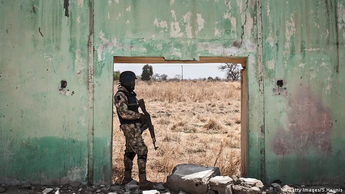 Nigeria Afrika Soldat steht in einem Türrahmen eines zerstörten Gebäudes