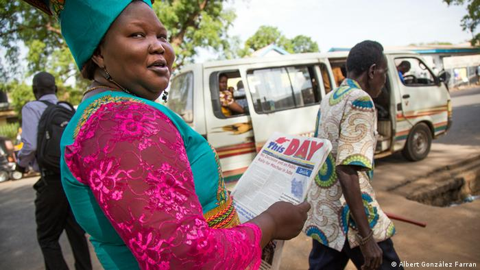 Josephine Achiro Fortelo reads a newspaper on one of the main streets of Juba (Albert González Farran)