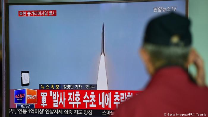 A man watches a TV news showing file footage of a North Korean missile launch