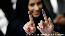 Two women show their fingers after voting