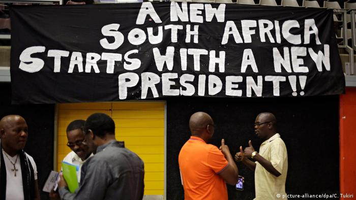 People stand in front of a sign that reads, A new South Africa starts with a new president.