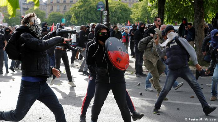 Masked youths hurl projectiles at police during a demonstration against a French labor law amendment.