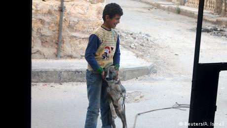Syrien Aleppo Junge spielt mit Hund