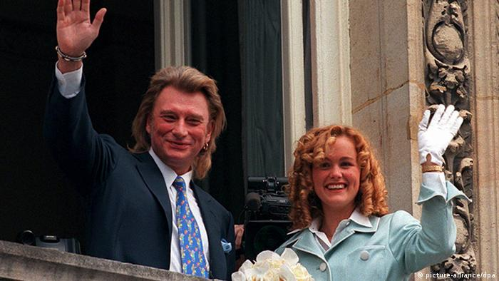 Johnny Halliday and Laetitia Boudou waving from a balcony in 1996 (picture-alliance/dpa)