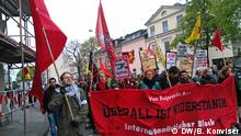 May Day protesters march through the streets of Bonn, carry banners, flags and placards.