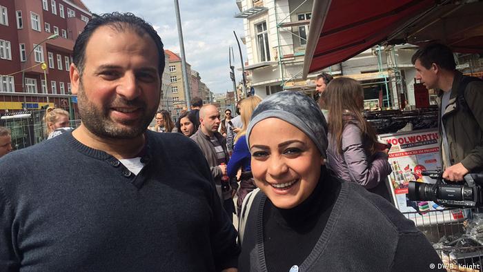 Homem com blusão escuro e mulher de lenço na cabeça na rua com várias pessoas ao fundo