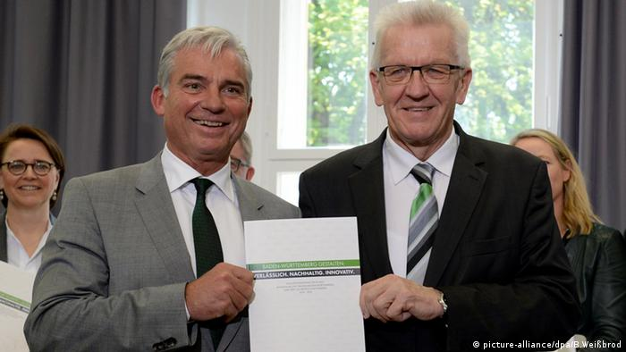 Green party head and Baden-Württemberg state premier Winfried Kretschmann stands next to CDU coalition partner Thomas Strobl