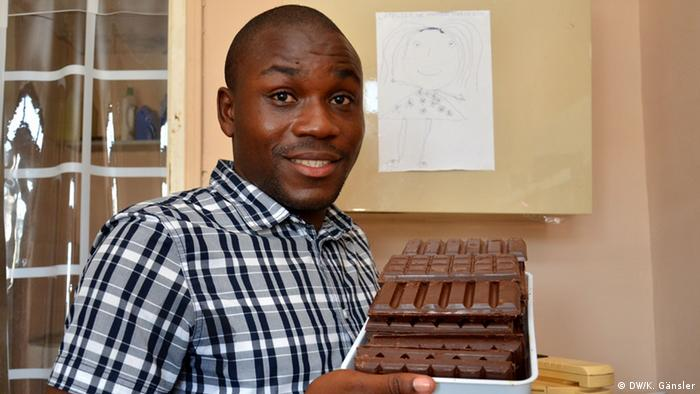 A man holds several bars of chocolates.