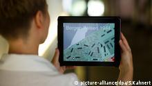 Eine Mitarbeiterin der Gedenkstätte Bergen-Belsen betrachtet am 05.09.2013 in Bergen-Belsen (Niedersachsen) den neuen multimedialen Geländeguide auf einem iPad. Ab dem 08.09.2013 können Besucher das ehemaligen Konzentrationslager mit einer neuen App, welche das Gelände dreidimensional rekonstruiert, erkunden. Foto: Sebastian Kahnert/dpa +++(c) dpa - Bildfunk+++   Verwendung weltweit © picture-alliance/dpa/S.Kahnert