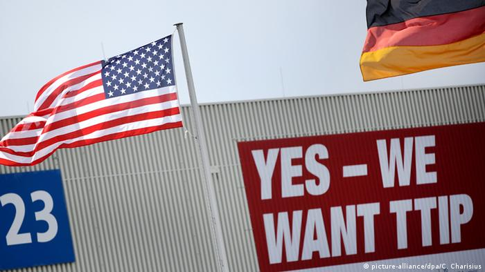 German and a US flags flying over the Hanover Fair, with a banner that reads 'Yes - We want TTIP' (Photo: picture-alliance/dpa/C. Charisius)