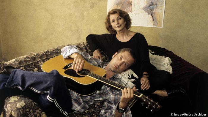 Filmszene aus 'MammaMia' mit Senta Berger. Senta Berger sitzt auf einem Bett. Auf ihrem Schoß liegt der Schauspieler Peter Lohmeyer mit einer Gitarre.