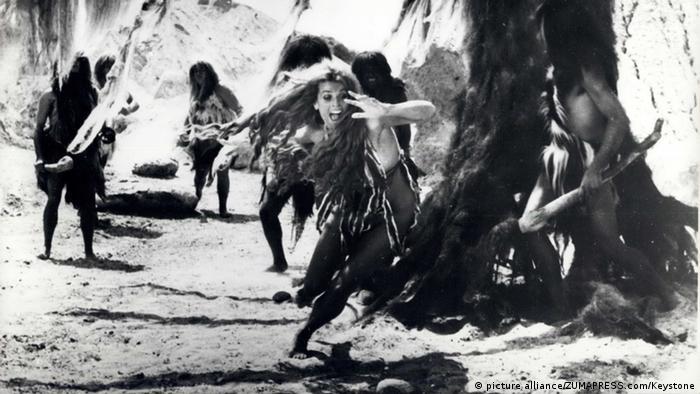 Szene aus dem Film 'Als die Frauen noch Schwänze hatten' mit Senta Berger, die halb bekleidet in einem Umhang vor Verfolgern davonrennt.
