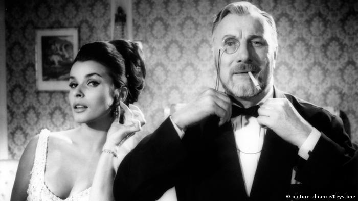 Szene aus dem Film 'Lange Beine - lange Finger' mit Senta Berger und Martin Held. Senta Berger trägt ein knappes Kleid und Martin Held einen Smoking.
