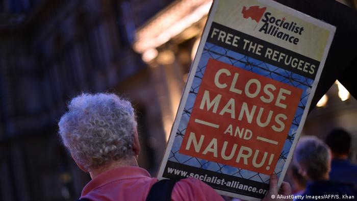 A participant holds a placard during a vigil in Sydney for an Iranian refugee who died after setting himself on fire on the Pacific island of Nauru