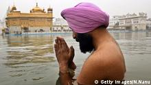 An Indian Sikh devotee prays as he takes a holy dip in the sarover - water tank - at the Sikh Shrine Golden Temple in Amritsar on January 1, 2013. Thousands of Sikh devotees from across India and abroad are preparing to pay obeisance on the occasion of New Year at the temple in northern India. AFP PHOTO/NARINDER NANU (Photo credit should read NARINDER NANU/AFP/Getty Images) © Getty Images/N.Nanu
