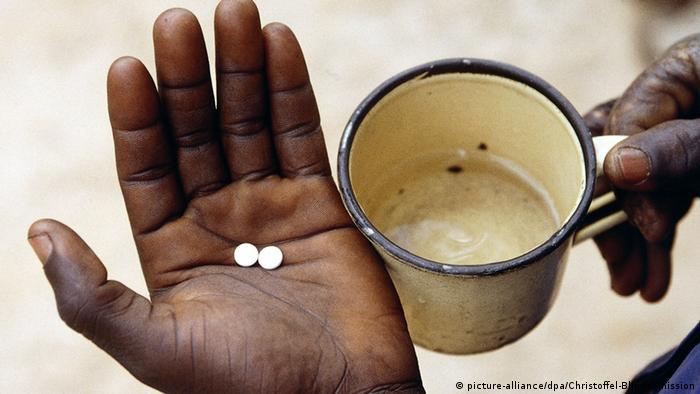 Zwei kleine, weiße Tabletten liegen in einer Hand, die andere rechts daneben hält eine Tasse mit Wasser