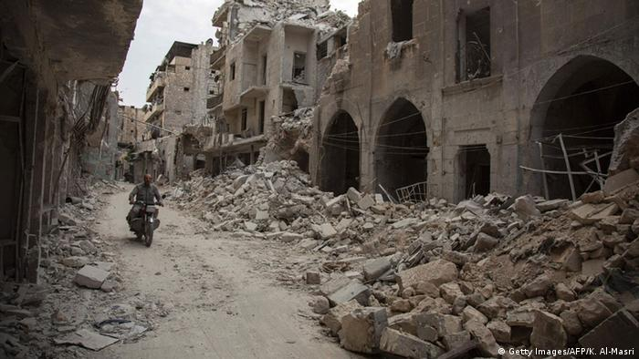 A Syrian man rides his motorbike past destroyed buildings on May 2, 2016 +++ Copyright: Getty Images/AFP/K. Al-Masri