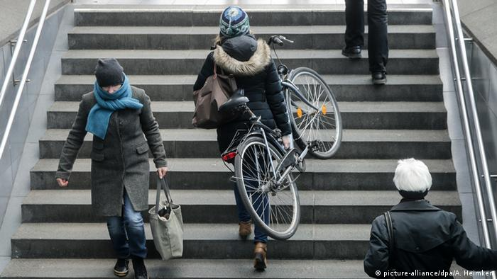 Женщина с велосипедом на лестнице метро