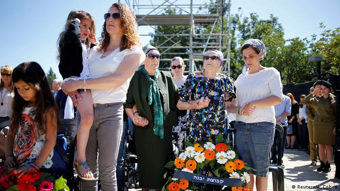 People stand still near wreaths as a two-minute siren marking Holocaust Remembrance Day is sounded at Yad Vashem Holocaust Remembrance Center in Jerusalem May 5, 2016.