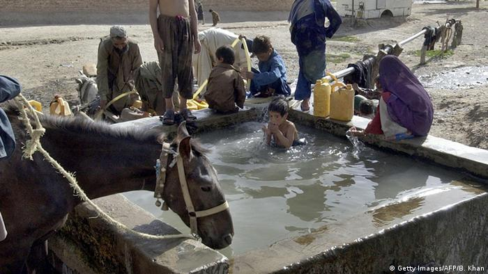 Pakistani residents fill their jerricans with water as a horse drinks water at a slum area in Quetta, 13 June 2007, as the country is in the grip of a scorching heat wave. Dozens of people have been killed from a sizzling heat wave lashing Pakistan since last week as temperatures have soared to more than 50 degrees Celsius (122 Fahrenheit) in some parts of the country (Photo: BANARAS KHAN/AFP/Getty Images)