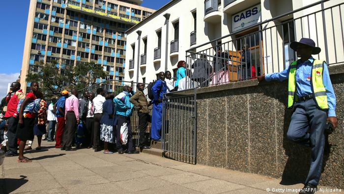 People cue outside an ATM in Zimbabwe.