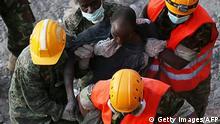 Rettungskräfte tragen einen der Überlebenden aus den Trümmern