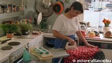 Symbolbild Frau in der Küche mit Bügeleisen