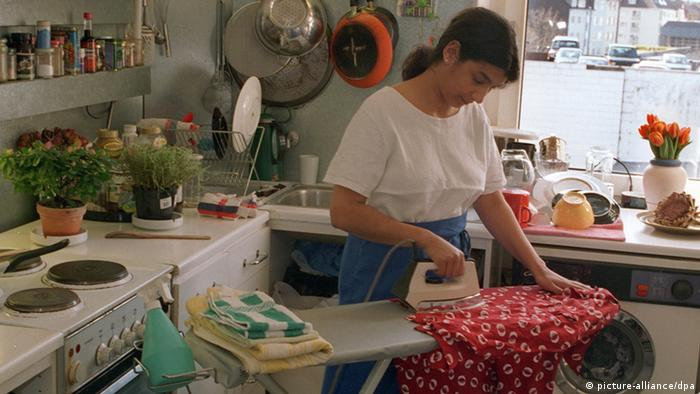A woman ironing in the kitchen