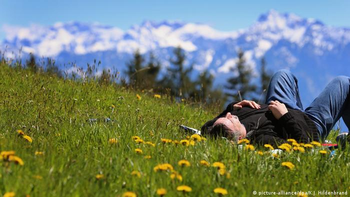 Hiker rests on a meadow in front of the panorama of the Alps